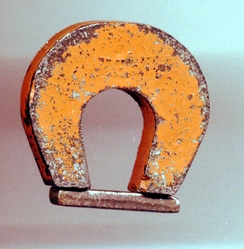 A magnet made of alnico, a ferromagnetic iron alloy, with its keeper.