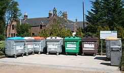 A recycling point in New Byth, Scotland, with separate containers for paper, plastics, and differently colored glass.