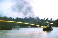 Riverboat of the U.S. Brown-water navy deploying an ignited napalm mixture from a riverboat-mounted flamethrower in Vietnam.