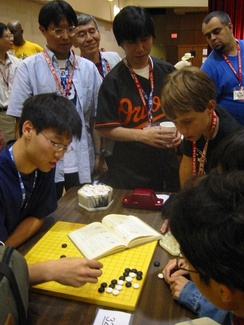 Three Japanese professional Go players observe some younger amateurs as they dissect a life and death problem in the corner of the board, at the US Go Congress in Houston, Texas, 2003.