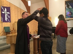 A Lutheran pastor distributes ashes to a communicant during a Divine Service