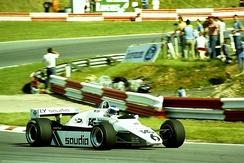 Sideview of a white Williams racing car going through a corner during a race