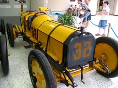 "Ray Harroun's Marmon ""Wasp"" with its rear-view mirror mounted on struts above the car on display in the Indianapolis Motor Speedway Hall of Fame Museum."