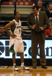 A man, wearing a brown suit, is talking to a basketball player on the side of a basketball court.