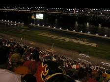 "Cars race by the ""DAYTONA"" letters during the 2005 Pepsi 400."