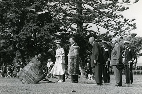 The Queen, accompanied by Prince Philip, is greeted with a pōwhiri before addressing a crowd. Waitangi, December 1953.