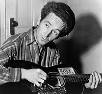 Woody Guthrie in 1943 with his guitar labeled This machine kills fascists