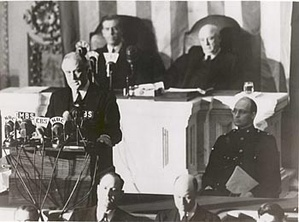 "President Roosevelt delivering the ""Infamy Speech"" to Congress, requesting a declaration of war, December 8, 1941.  Behind him are Vice President Henry Wallace (left) and House Speaker Sam Rayburn. To the right, in uniform in front of Rayburn, is Roosevelt's son James, who escorted his father to the Capitol."