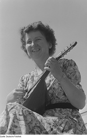 A woman playing a bowlback mandolin in Germany in 1952.
