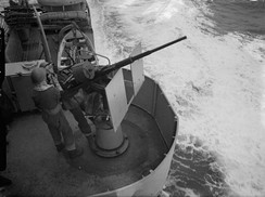 A Royal Navy Oerlikon gunner at his gun mount aboard the Dido-class cruiser HMS Dido in 1942