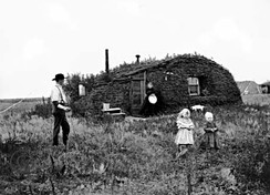 Norwegian settlers in North Dakota in front of their homestead, a sod hut