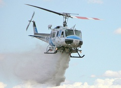 A Bell 205 dropping water onto a fire