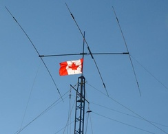 The top of a tower supporting a Yagi-Uda antenna and several wire antennas, along with a Canadian flag