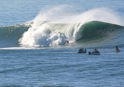 Photo of taller-than-human-sized wave breaking with several watching surfers in foreground