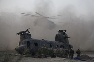 A Marine Heavy Helicopter CH-53E Super Stallion lands next to a downed Canadian Forces CH-47 Chinook during a tactical recovery of aircraft and personnel mission in Kandahar Province.