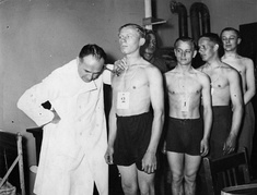 Men standing in line waiting for a medical check
