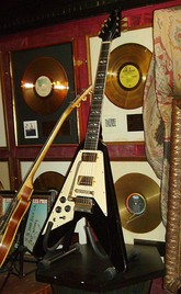A color photograph of a black Gibson Flying V guitar