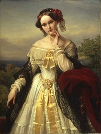 A three-quarter length portrait of a young white woman in the open air. She wears a shawl over an elaborate long-sleeved dress that exposes her shoulders and has a hat on over her centrally parted dark hair.