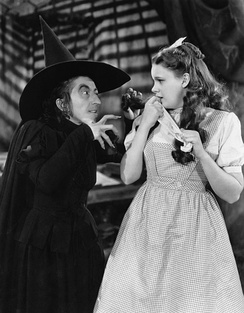Margaret Hamilton as the Witch in the 1939 film version, threatening Dorothy (Judy Garland)