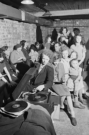 A young woman plays a gramophone in an air raid shelter in north London during 1940