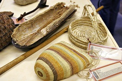 Aboriginal women's implements, including a coolamon lined with paperbark and a digging stick. This woven basket style is from Northern Australia. Baskets were used for collecting fruits, corms, seeds and even water – some baskets were woven so tightly as to be watertight.