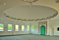 The ladies' prayer hall in the Khadija Mosque in Berlin; upper part reads: Only in the remembrance of Allah will your hearts find peace (in Arabic)