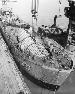 The hangar for the supersonic Regulus II cruise missile being installed aboard USS King County (AG-157), a Landing Ship, Tank (LST) converted to an experimental guided-missile testing ship, on 5 April 1957. USS YD-33 is doing the lifting.