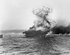 The aircraft carrier USS Lexington explodes on 8 May 1942, several hours after being damaged by a Japanese carrier air attack.