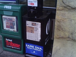 A newly redesigned and installed street vending box for The Oregonian (black) after the paper became a tabloid on April 2, 2014, along with a Portland Tribune box (green)