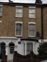 exterior of white house, with blue plaque on front wall