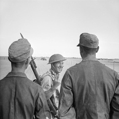 A British soldier puts his fingers up at German prisoners captured at El Alamein, 26 October 1942
