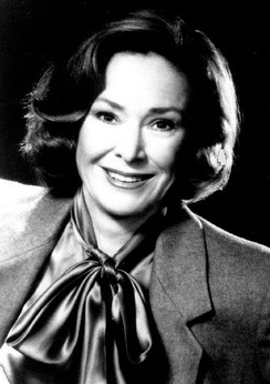 Black and white photo of a smiling woman about fifty years of age and wearing a jacket and tied-up scarf