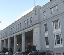 Facade of a large white building, the left having large pillars beneath a strip with dozens of windows and the right three stories of large windows.