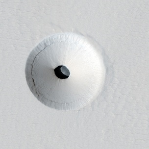 Cropped version of a HiRISE image of a lava tube skylight entrance on the Martian volcano Pavonis Mons.