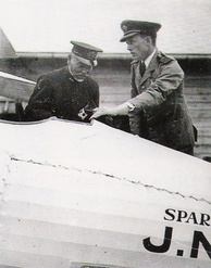 Two men standing over the interior of an airplane's cockpit