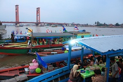 Floating warung boat attached to the bank of Musi river, Palembang, selling local favourite such as pempek.
