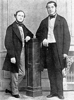 Black-and-white image of two middle-aged men, either one leaning with one elbow on a wooden column in the middle. Both wear long jackets, and the shorter man on the left has a beard.