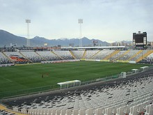 "A semi-panoramic view of the stadium. The seats are white and black, and shows the club badge in the seats. The roof of the stand is supported by a cantilever structure, in a ""buried"" construction."