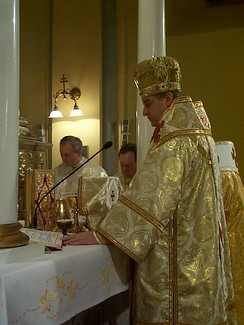 A bishop celebrating Divine Liturgy in a Greek-Catholic church in Prešov, eastern Slovakia. Another bishop stands to his immediate right (white omophorion visible), and two married priests stand to the side (facing camera).
