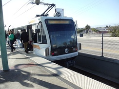 Westbound Metro Green Line train to Redondo Beach Station arrives at Long Beach Boulevard Station.