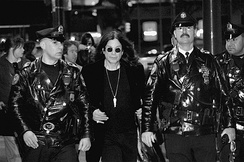Osbourne, flanked by Philadelphia police officers, leaves Borders in Center City after signing copies of his autobiography, I Am Ozzy on 27 January 2010.
