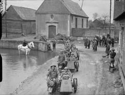 Motorcycle combinations of the 4th Battalion, Royal Northumberland Fusiliers pass through a village, watched by the local inhabitants, France, 20 March 1940.