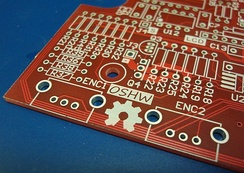 The OSHW (Open Source Hardware) logo silkscreened on an unpopulated PCB