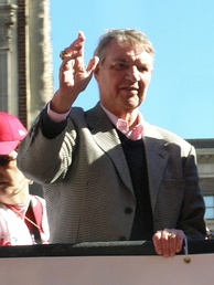 A white-haired man in a tweed jacket, dark sweater, and a pink dress shirt waves from atop a truck.