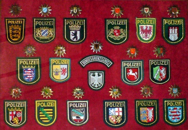 Sleeve and cap ensigns of the 16 state police forces and the former Bundesgrenzschutz (Federal Border Guard)