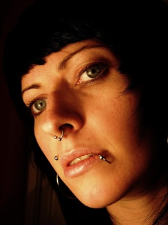 Person with several facial piercings (Monroe, Septum and Lip)