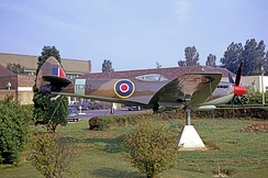 The RAF Kemble main entrance area in 1967 with a pre-war hangar in the left background and a Spitfire as gate guardian