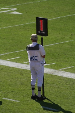 A down marker showing first down along the sideline of a collegiate game