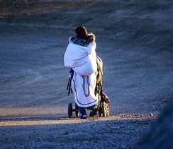 An Inuit woman uses a traditional amauti and a modern western stroller