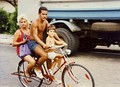 A family of three sharing a bicycle in 1994.